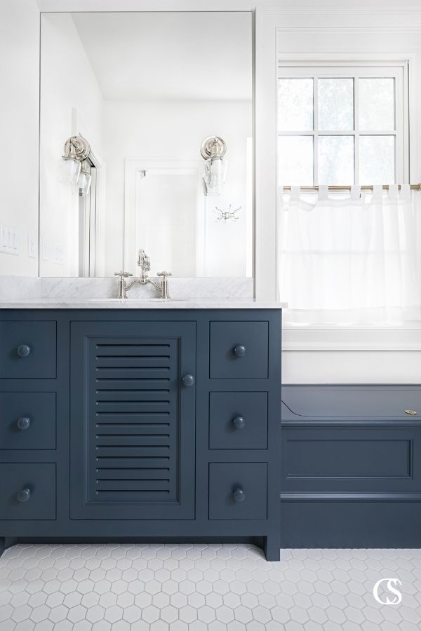 These blue custom bathroom cabinets create an incredible and classic contrast to the white flooring and walls.