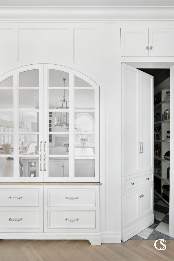 "Some of the best custom cabinets designed for the kitchen incorporate pieces that aren't actually cabinets at all—like this ""hidden"" door to the pantry."