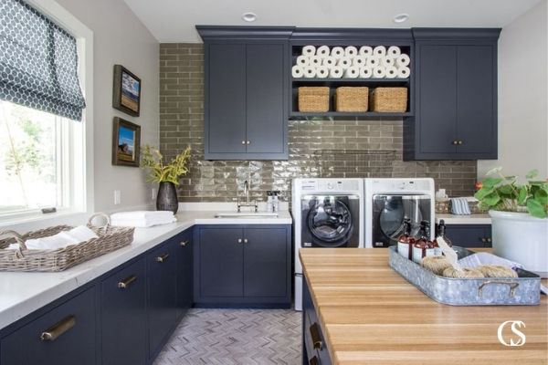 I love this laundry room! One, for its moody take on a household task and two, because it has some of the best design ideas for cabinets in the laundry room—like pull out cabinets for each family members' clothes hamper!