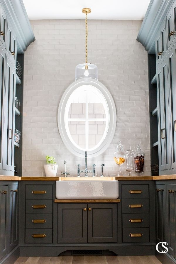 This custom pantry design included custom cabinets, brass hardware, and oak countertops with plenty of space for style and storage.