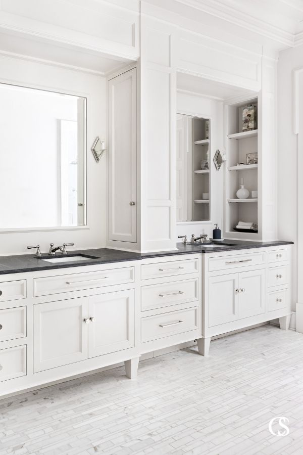 The white aesthetic is a complete classic. These custom bathroom cabinets play perfectly with a unique tile floor and large mirrors to create even more white space.