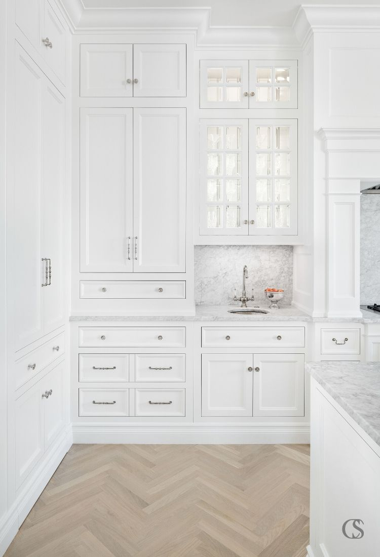 How many different styles of hardware can you spot in this custom cabinet design for the kitchen? Mixing and matching similar drawer pulls and handles is a beautiful way to spice up an all white kitchen.