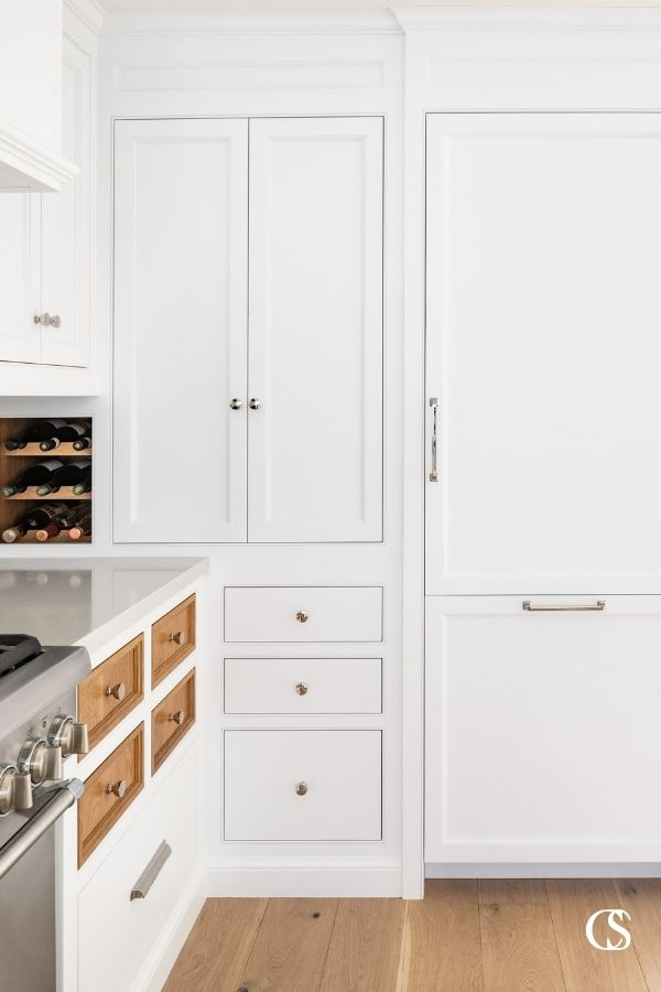 Who says every drawer and cupboard door have to match? These custom kitchen cabinet doors feature contrasting stained wood against the rest of the white painted cabinets, to great effect!
