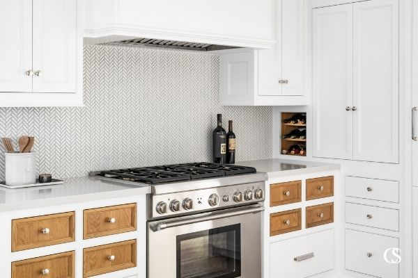 Who says every drawer and cupboard door have to match? This custom kitchen cabinet design features contrasting stained wood against the rest of the white painted cabinets, to great effect!