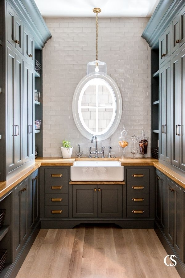 This custom pantry design includes custom cabinets, brass hardware, and oak countertops with plenty of space for style and storage.