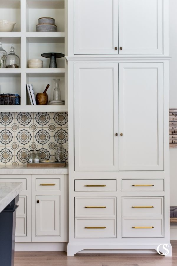 We love the mix of hardware styles mixed with a detailed tile backsplash in this set of custom kitchen cabinets and an open concept living room.