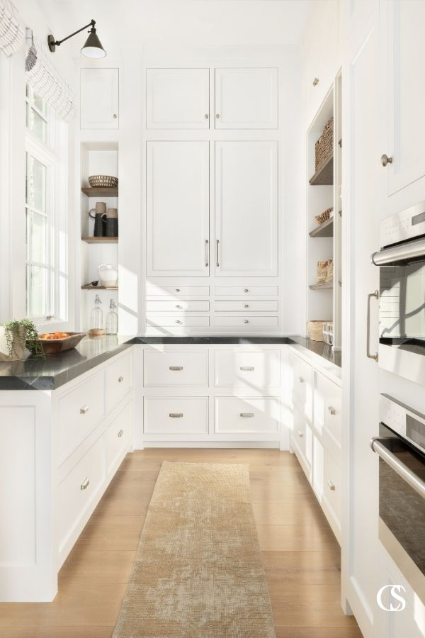 What kitchen pantry design ideas are running around in your head? This pantry sings of organization with a combination of open shelves, usable counter space, and beautiful custom inset cabinetry.