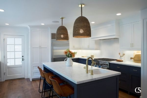 Creating a unique custom kitchen doesn't have to mean straying from a standard (and working!) kitchen layout. Make a statement with blue custom kitchen cabinets paired with white uppers to bring light into the space.