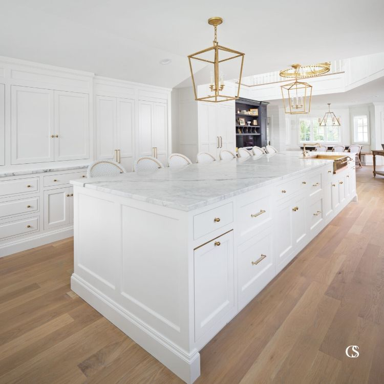 This white kitchen island design is large enough to comfortably seat 8 people which means it also has plenty of room for cooking, entertaining, and storage.