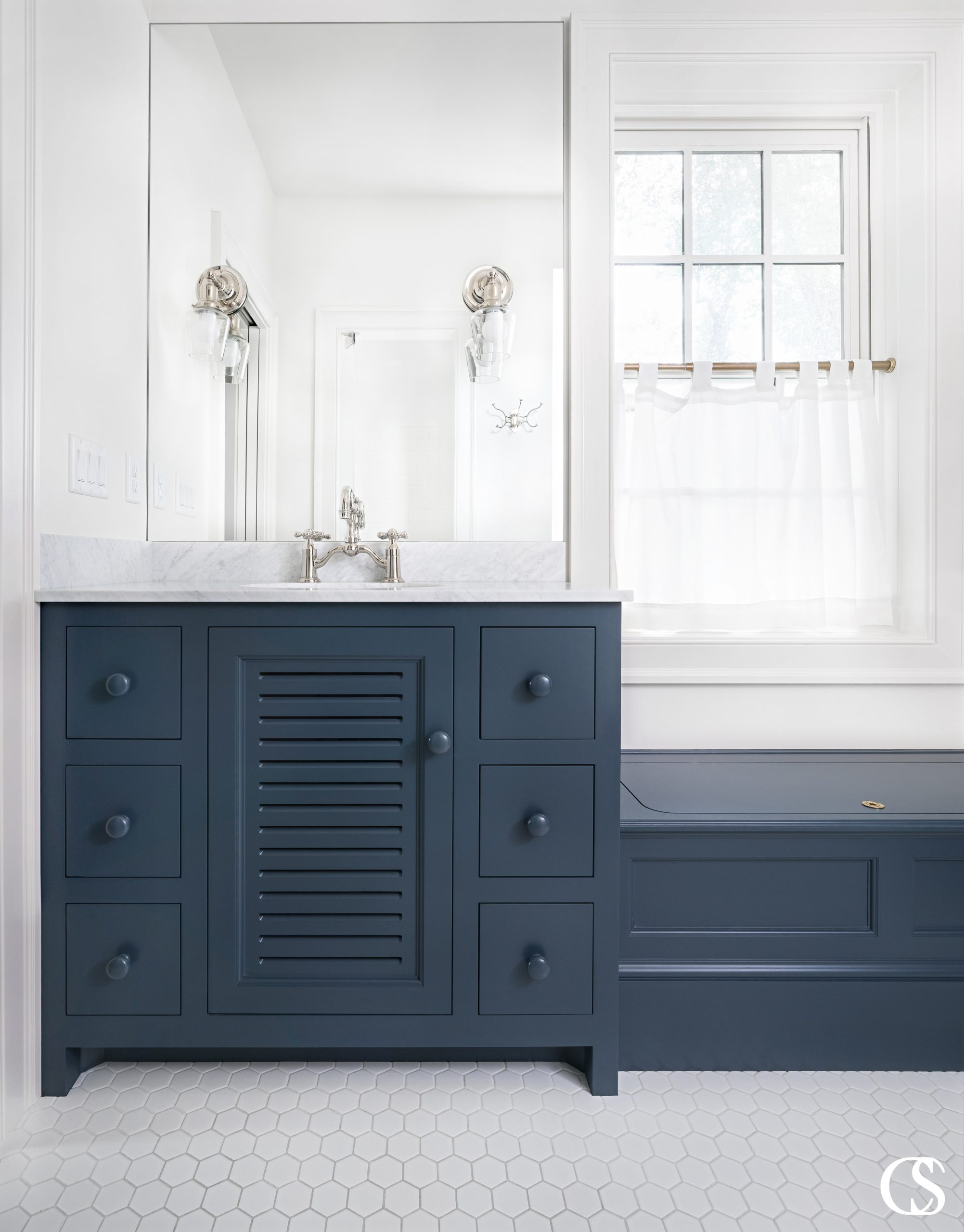 What could become a bulky bathroom cabinets design is completely changed by the slats in the center cupboard door. It's the little decisions like that which take custom cabinetry to the next level.