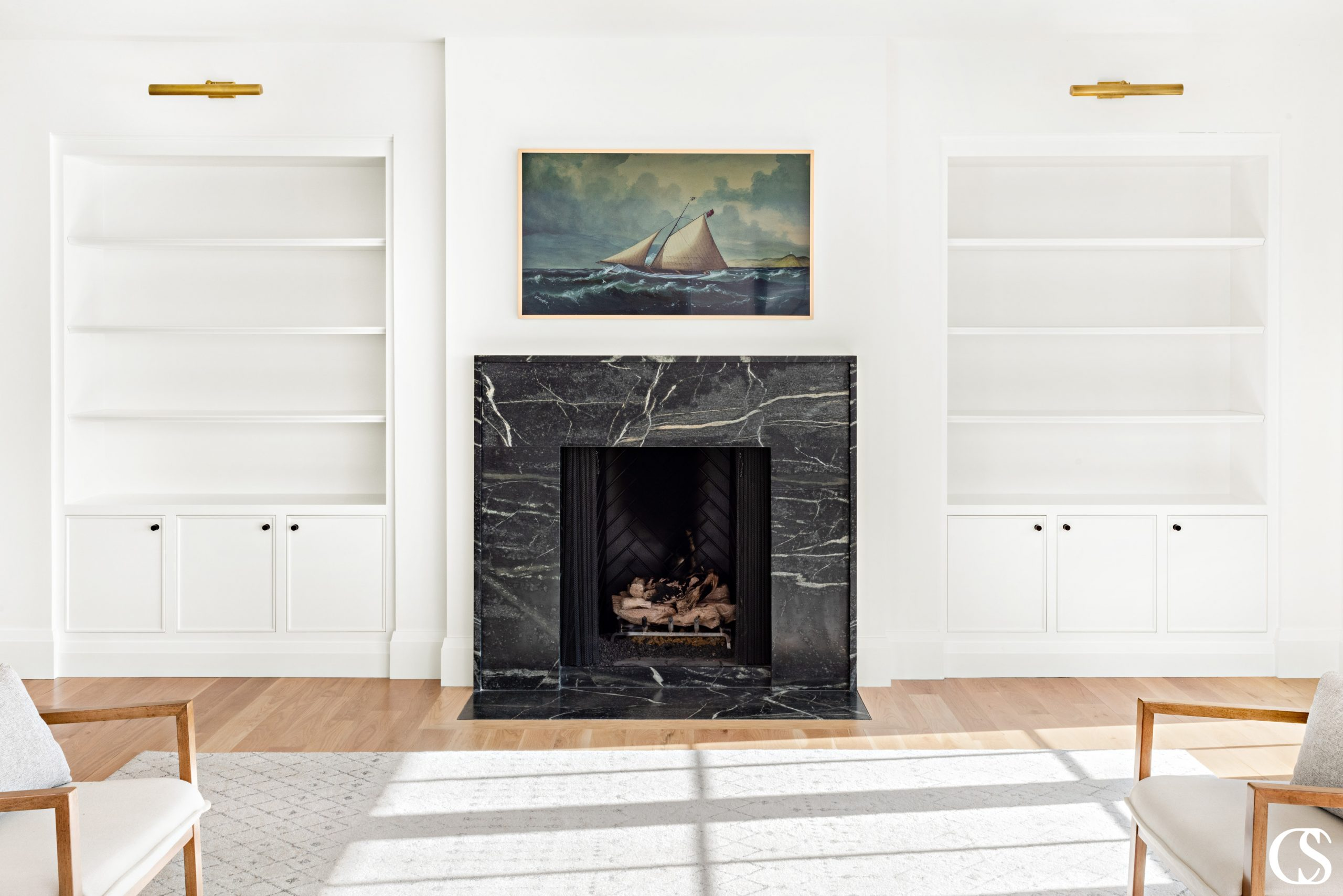 Designing custom cabinets for the home often means making them feel like they belong, like they've always been part of the house plans—like these sleek built-in cabinets flanking the marble fireplace.