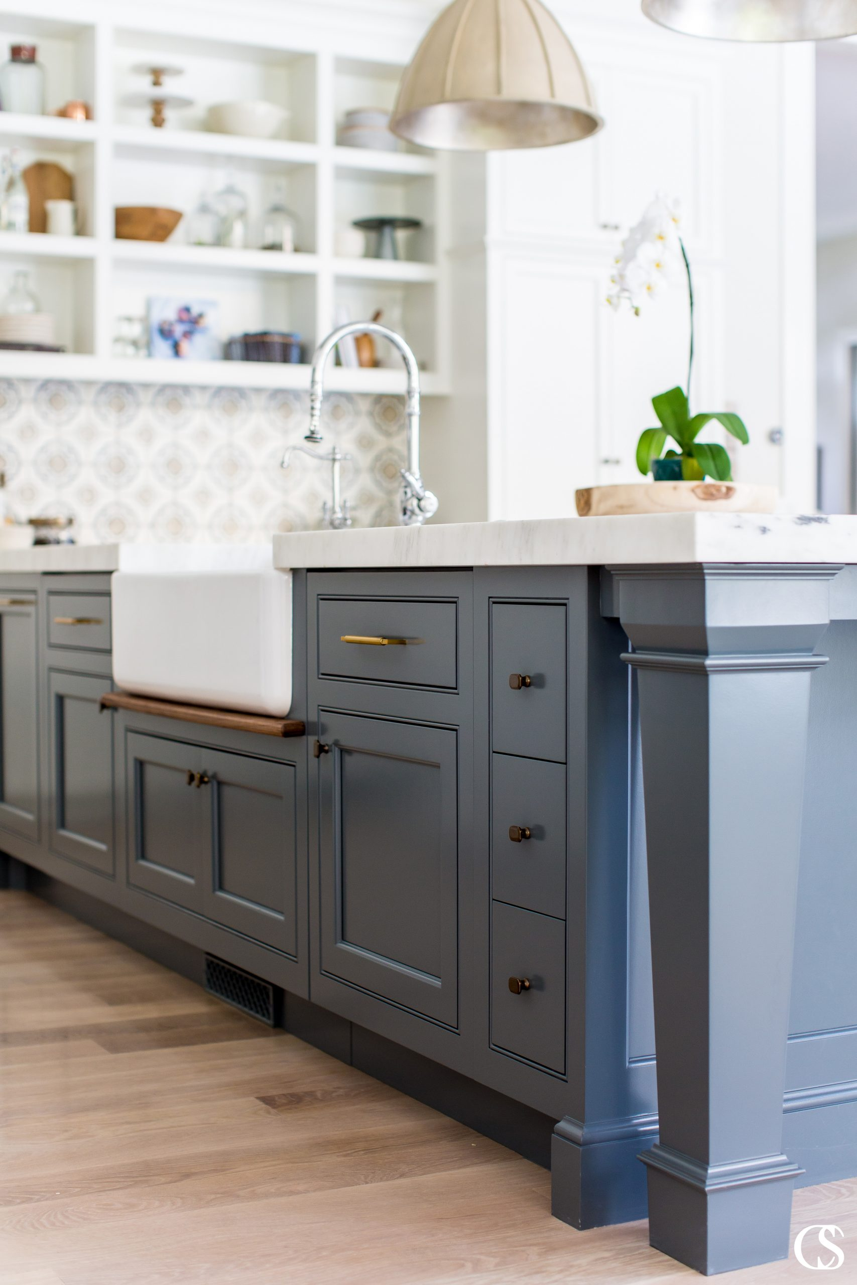 It's amazing how some open kitchen shelves can balance the weight of this blue kitchen island design. It almost creates an anchor for the room so great kitchen lighting and custom wall tile can really pop.