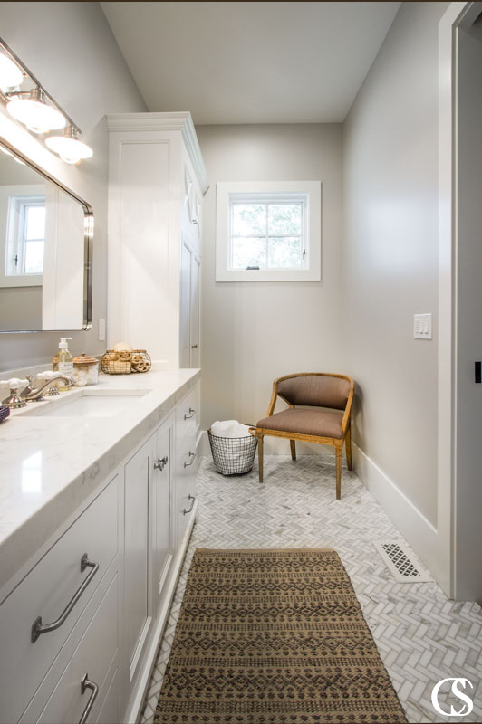 The best custom bathroom design makes use of any space you've got available, like with a sleek vanity cabinet and full wall armoire for additional storage.