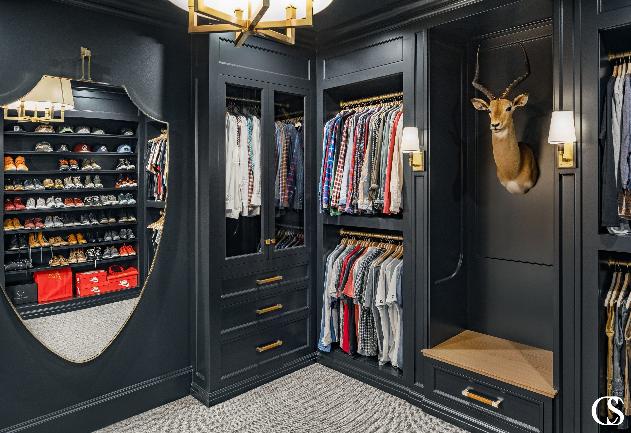 Don't ever think that custom built in cabinet closet design is just for the ladies. This man cave of a dream closet is moody and makes every hat, shirt, and pair of shoes pop.