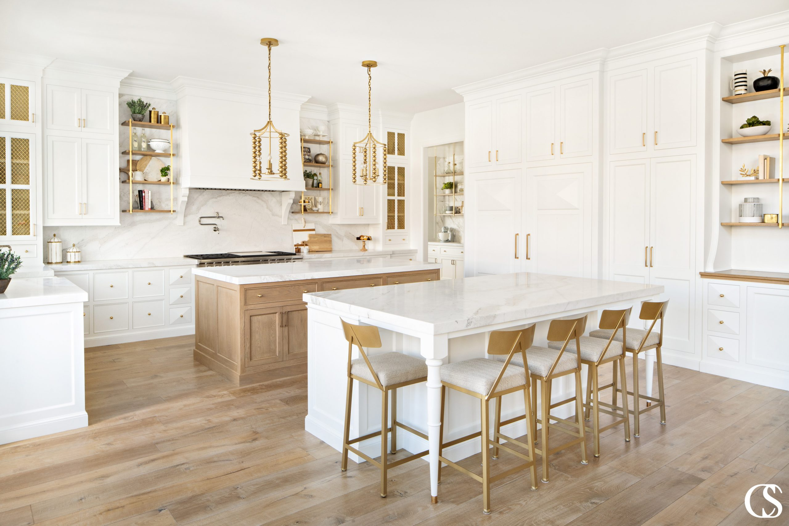 Open shelving, mullioned cupboards, hidden refrigerators, and a double island set up all come together in some of the best custom cabinet design for a kitchen.