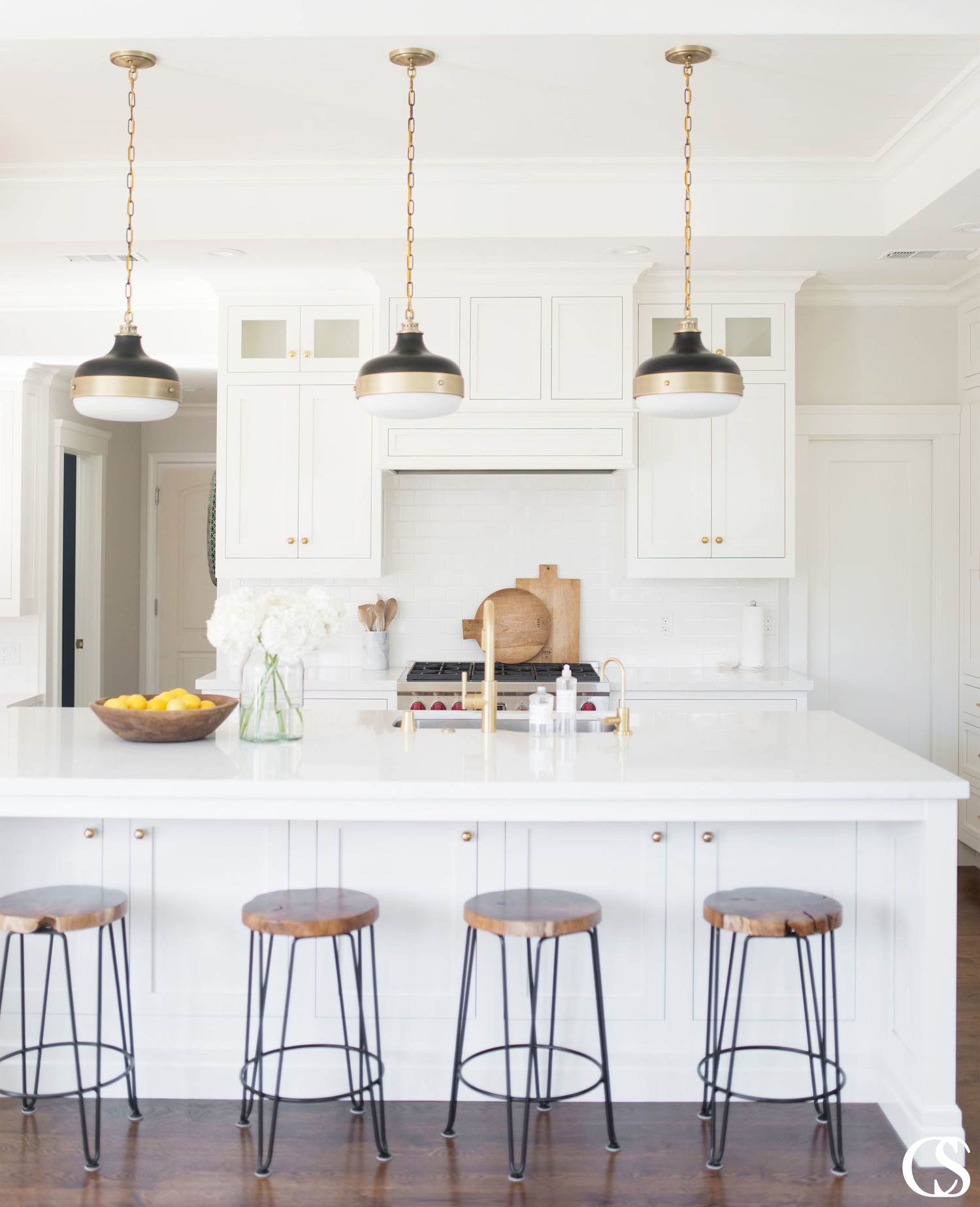One of the great things about custom white kitchen cabinets is that they can hide more than you might think. Like this custom kitchen island for example—the perfect shade of white paint for the kitchen helps disguise extra storage in front of bar stools.
