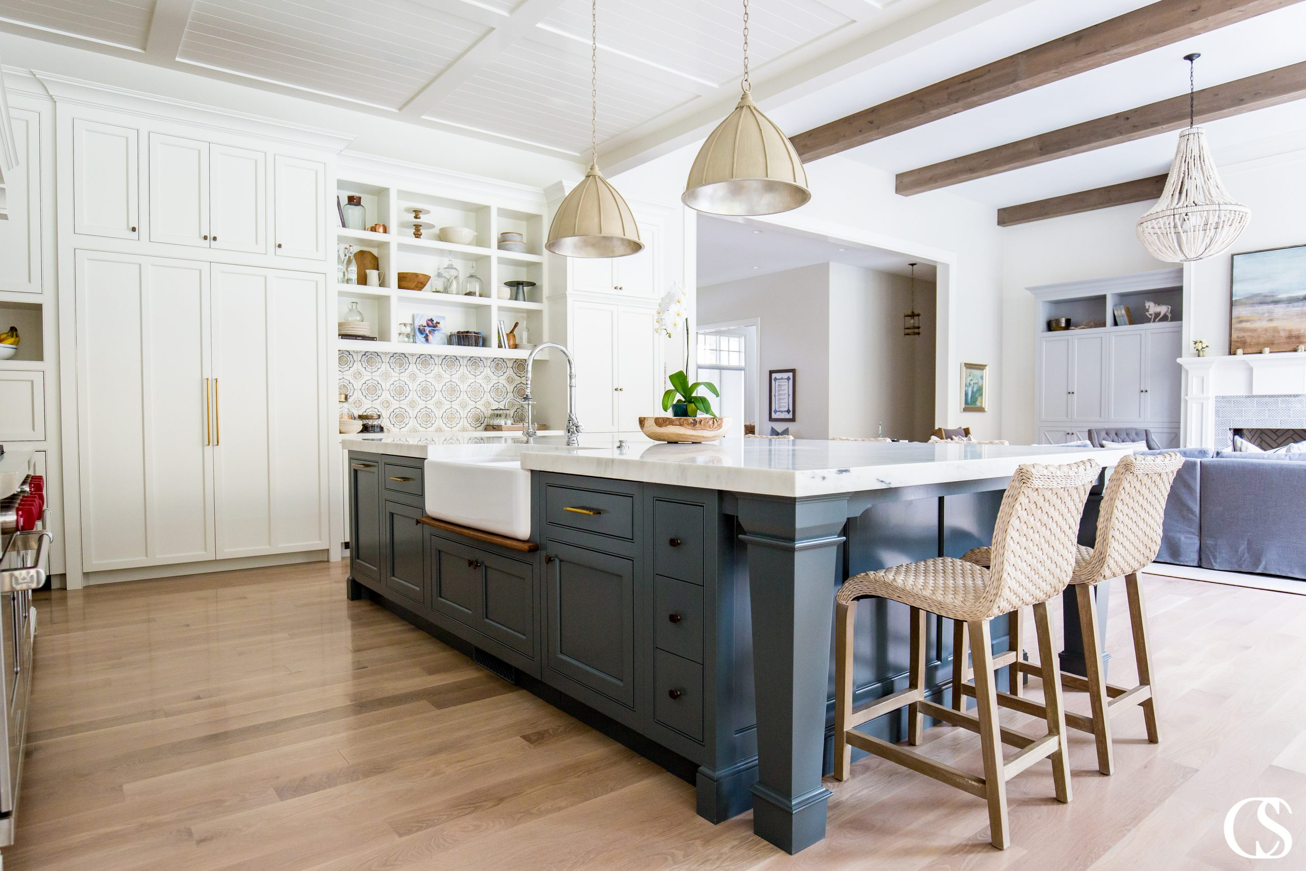 This big kitchen island design in one of our favorite blue custom kitchens becomes a focal point of the space but also serves as a separator between kitchen and living rooms, making each space its own while coordinating beautifully.
