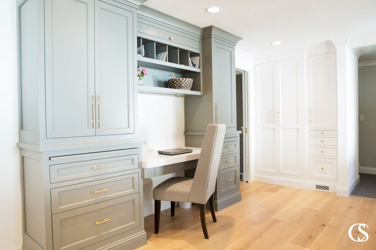 """This built in cabinet for a home office sits right between the kitchen and laundry """"room"""" hiding behind those white custom built ins. It's a great way to utilize every inch of a space."""