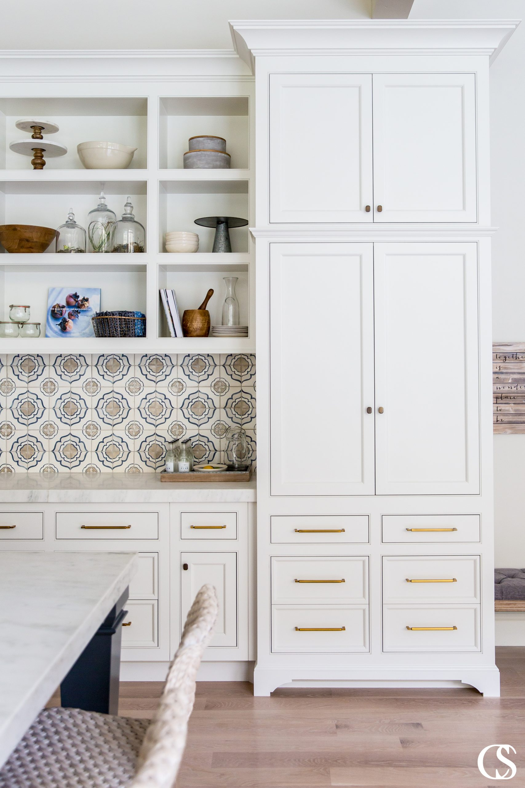 We love the mix of hardware styles mixed with a detailed tile backsplash in this set of custom cabinets for the kitchen and an open concept living room.