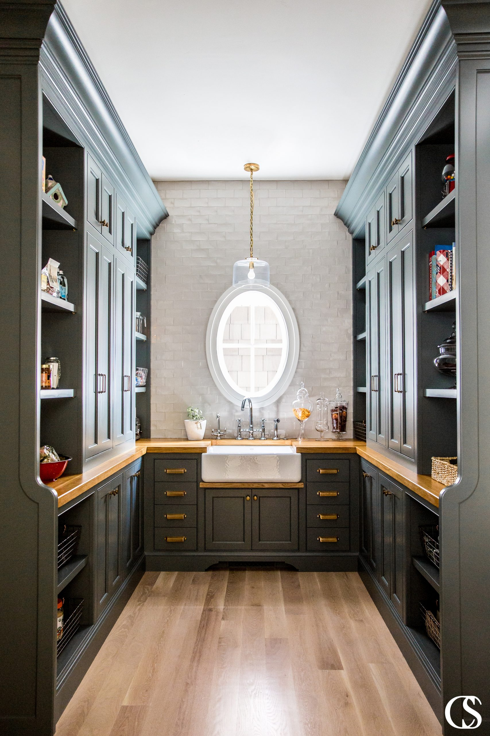 This pantry design included custom black cabinets, brass hardware, and oak countertops with plenty of space for style and storage.