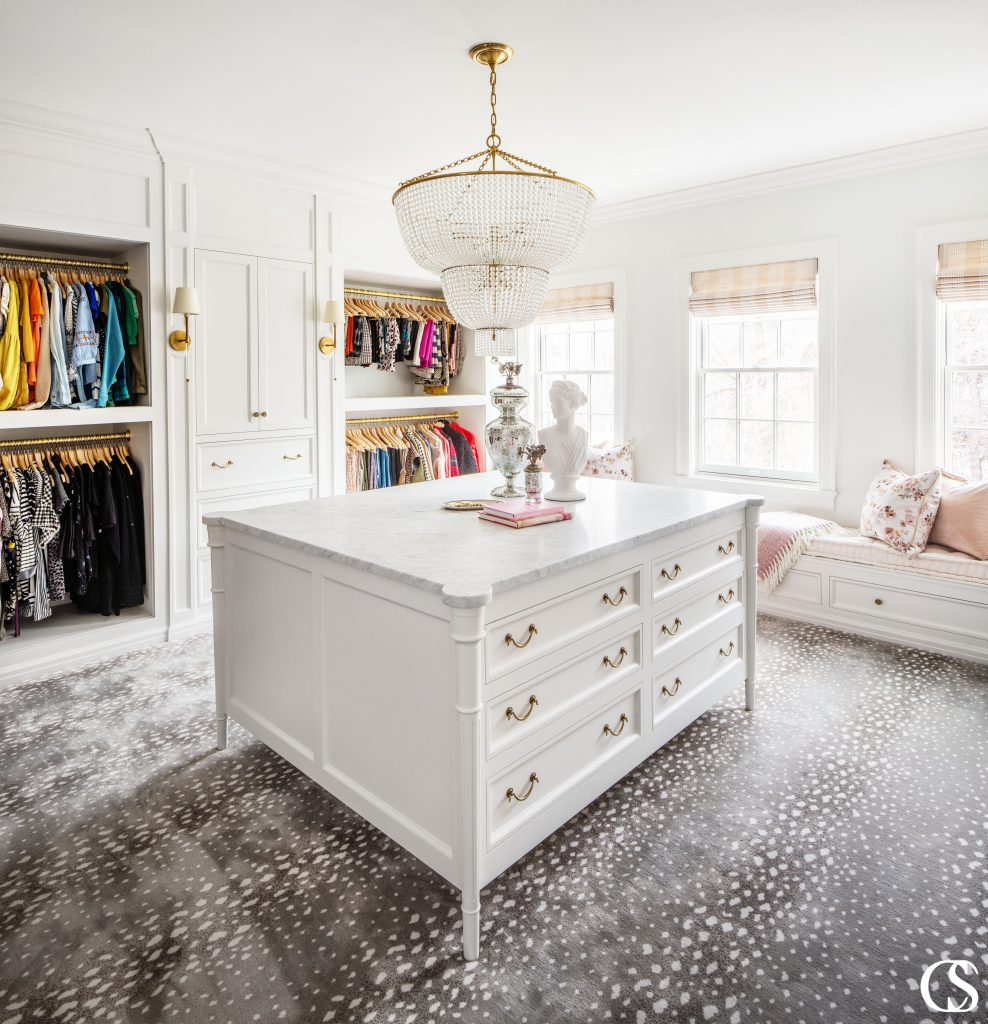 This light and airy custom closet design stays grounded with deep gold accents, a heavy marble countertop on the central built in cabinet, and a fashionable printed carpet.