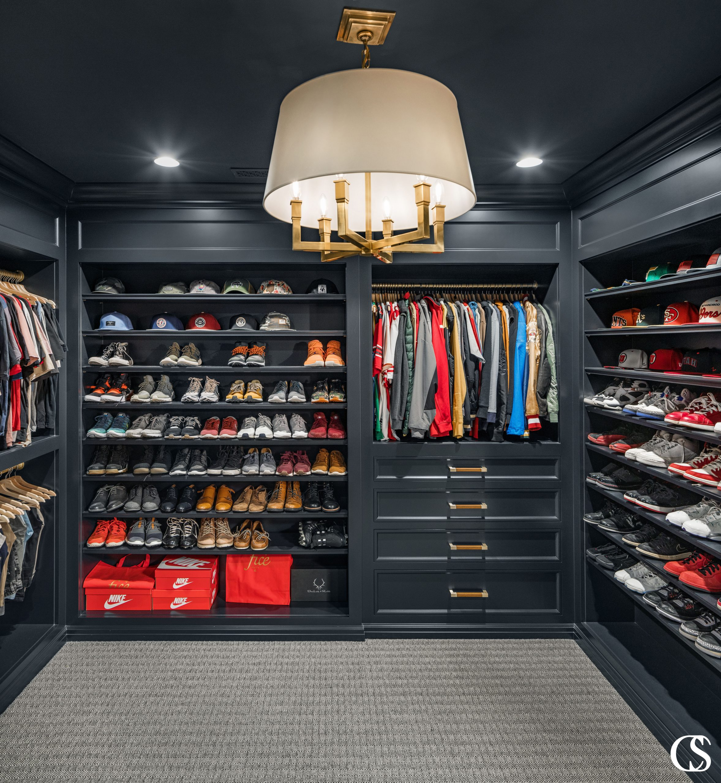 Don't ever think that custom built in cabinet closet design is just for the ladies. This man cave of a dream closet is moody and makes every hat, jacket, and pair of shoes pop.