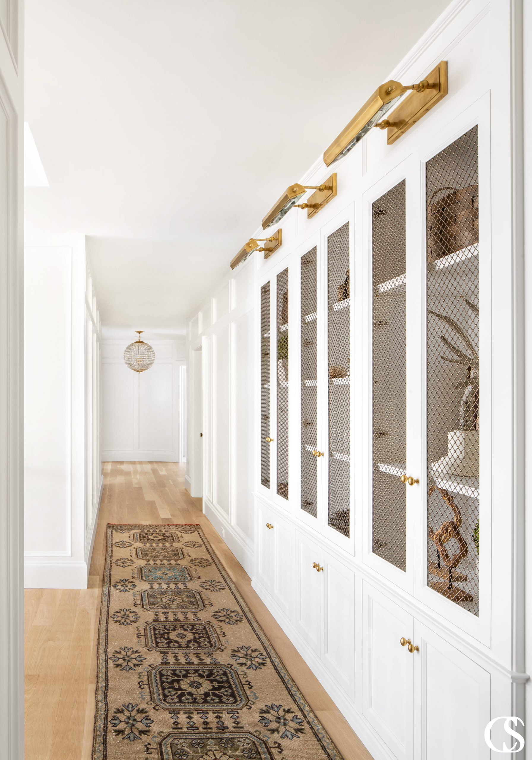 Make a hallway more than just bare walls and doorways with custom built in design like this! It's a beautiful way to create space and add character to a home.