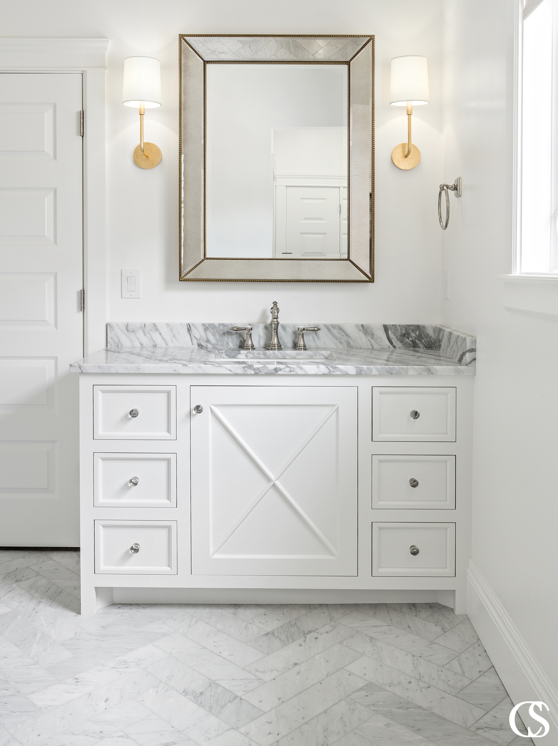 The best custom bathroom cabinet design can combine multiple aesthetics, like the modern and farmhouse looks you see coming together in this white bathroom vanity.