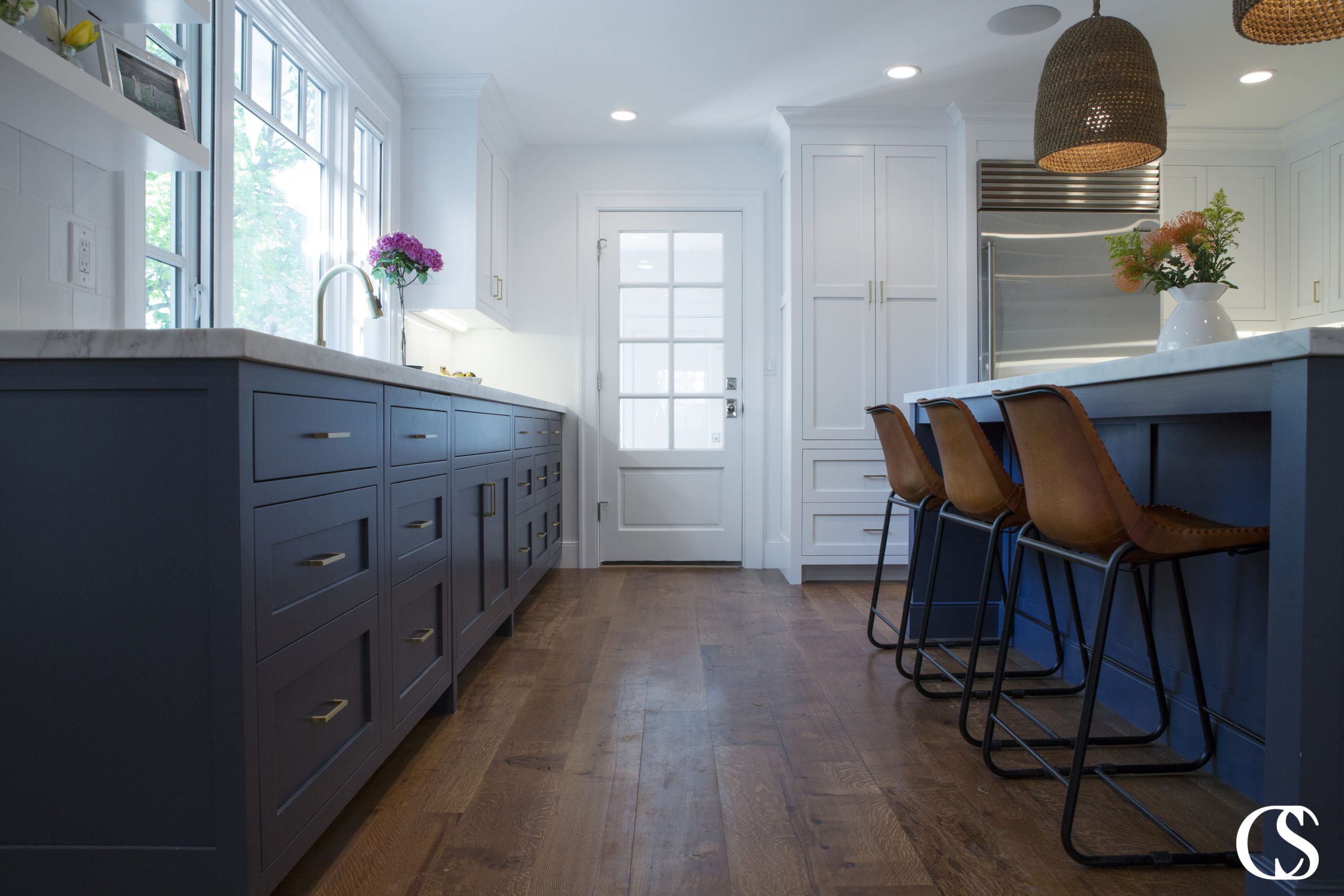 Blue kitchens are popular for a reason! Hale Navy helps these custom kitchen cabinets play perfectly with the white walls and upper cabinetry as well as the warmer tones found in the floor and chairs.
