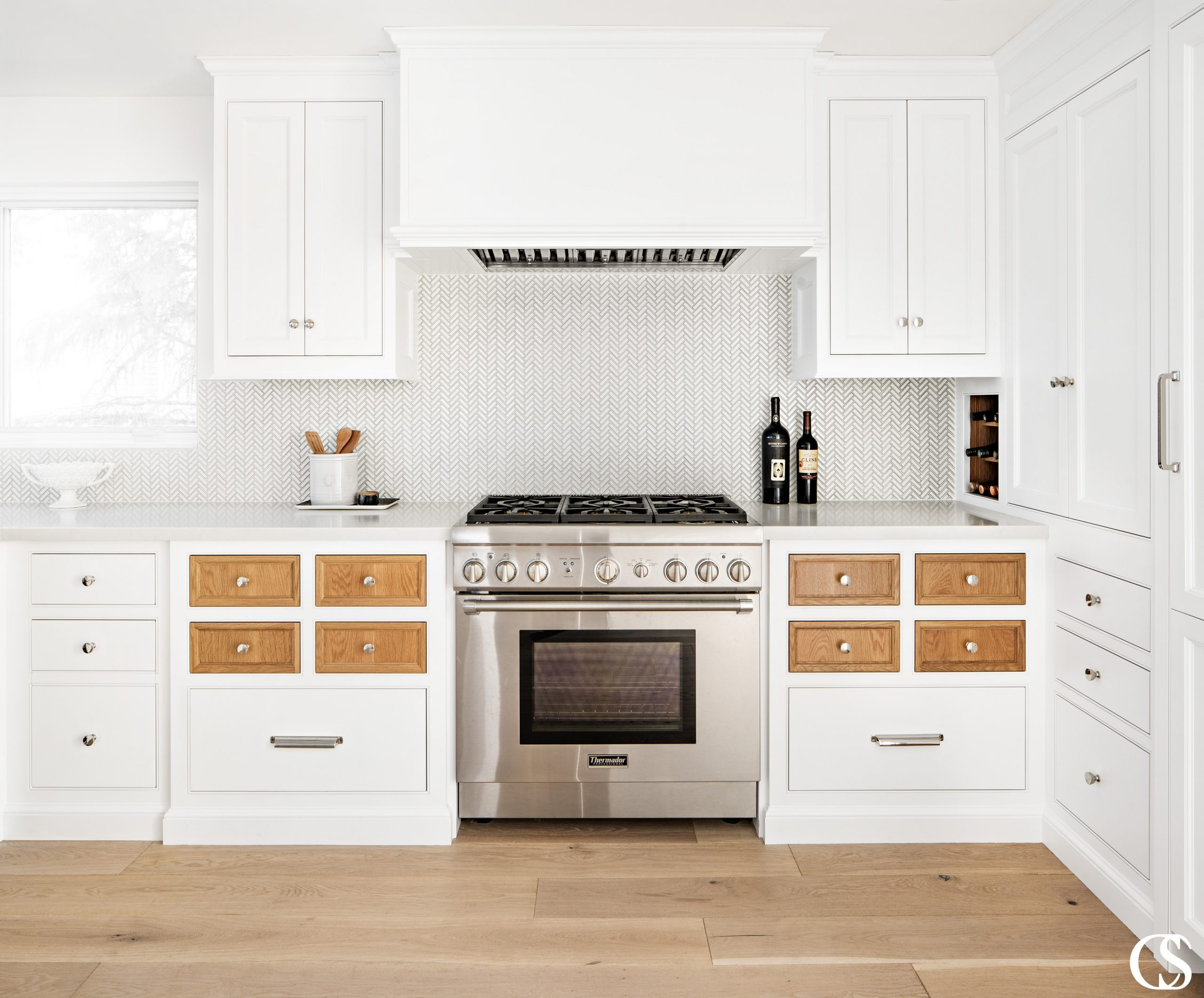Who says every drawer and cupboard door have to match? These kitchen cabinet doors feature contrasting stained wood against the rest of the white painted cabinets, to great effect!