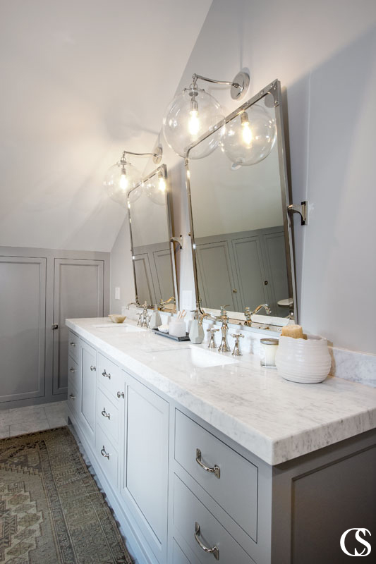 Creating a unique custom cabinet design for your bathroom means working with every single quirk of the space—even angular walls like this one.