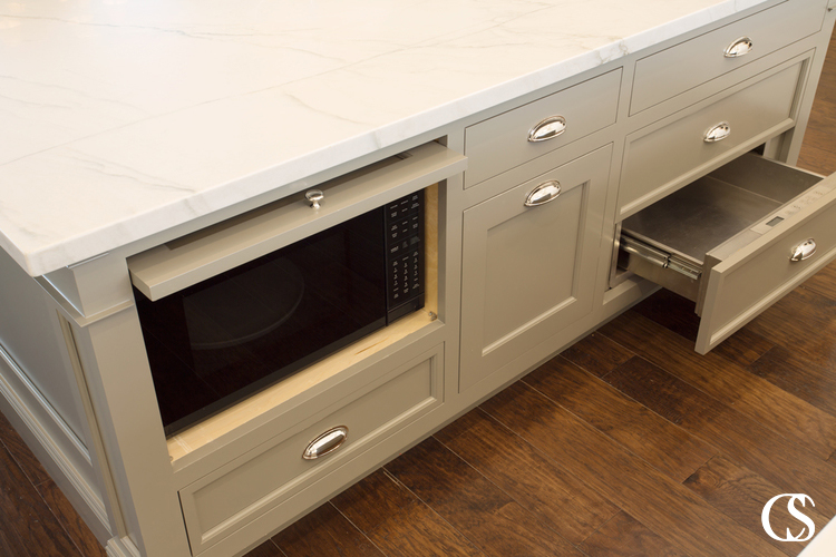 Custom kitchen cabinets can help make precious room on countertops by tucking away appliances like the microwave.