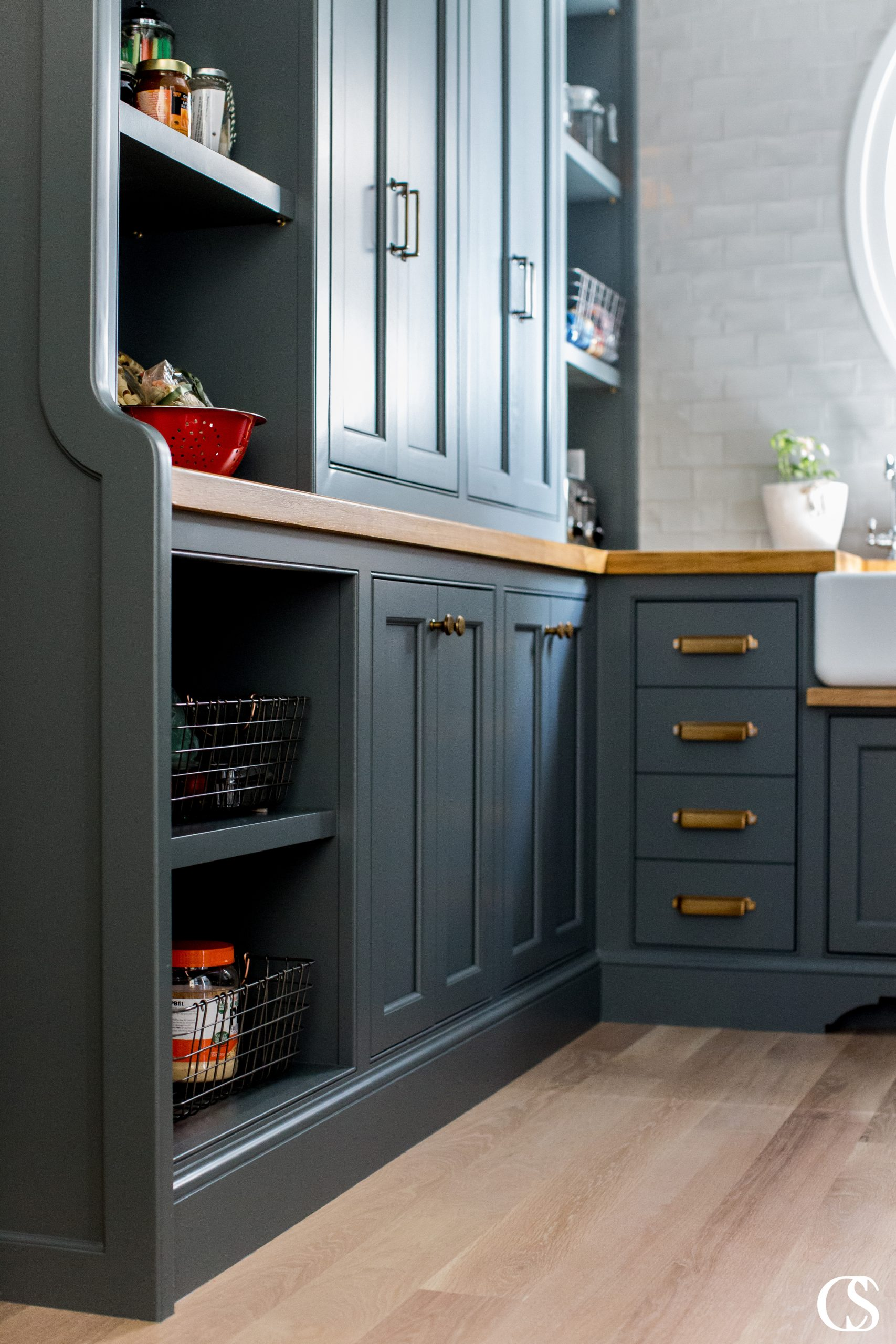 This custom kitchen pantry design idea included moody black cabinets, brass hardware, and oak countertops with plenty of space for style and storage.