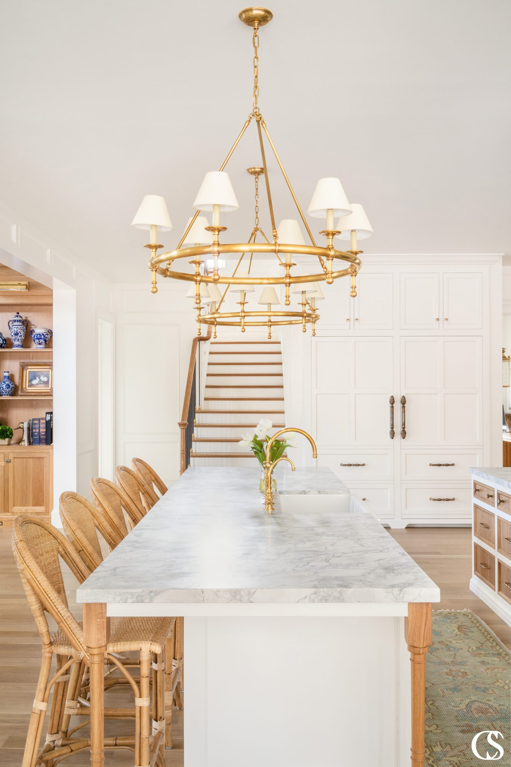 Custom kitchen cabinet design extends beyond your basic cupboards and drawers—think in terms of a kitchen island, wall built-ins, and even complementary display built ins in the next room.