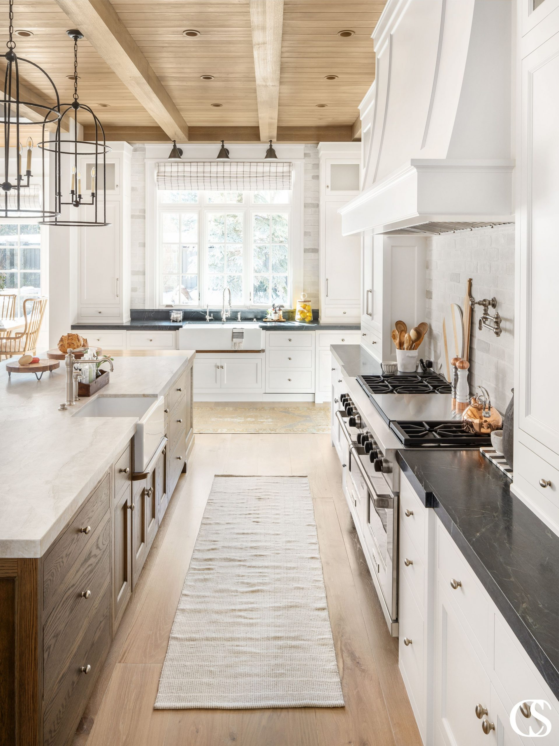 The natural woods in this white custom kitchen brings a certain homey balance to the space. It's cozy yet bright and clean.