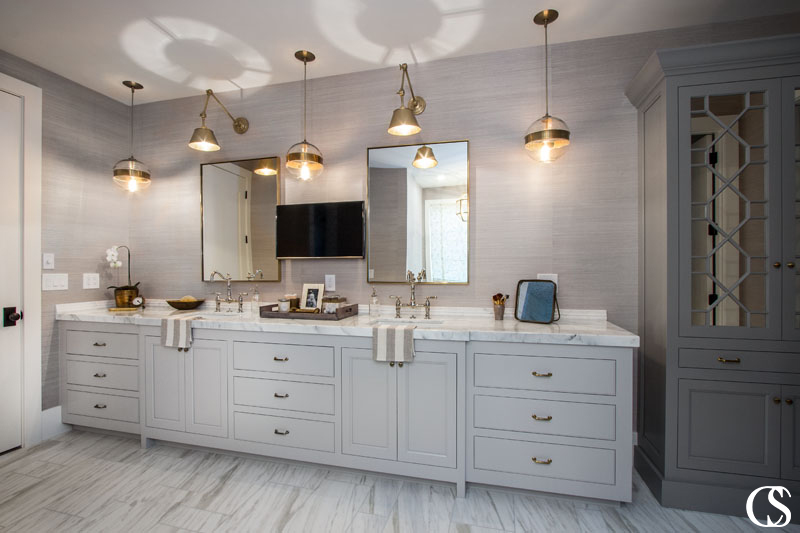 Balancing out popular greige with a deeper color on another cabinet increases dimension and character in any cabinet design—like these unique bathroom cabinets.