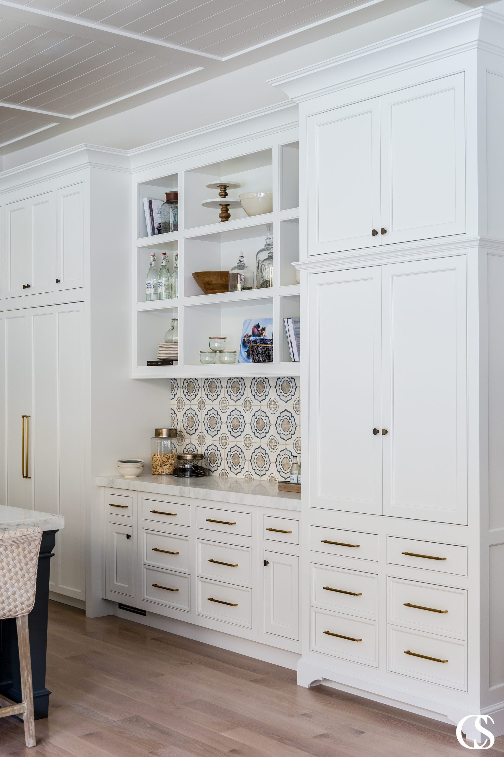 This unique custom kitchen cabinet design conjures memories of a vintage kitchen while offering complementary modern elements to balance out the look. Dare you not to dream of that custom tile backsplash!