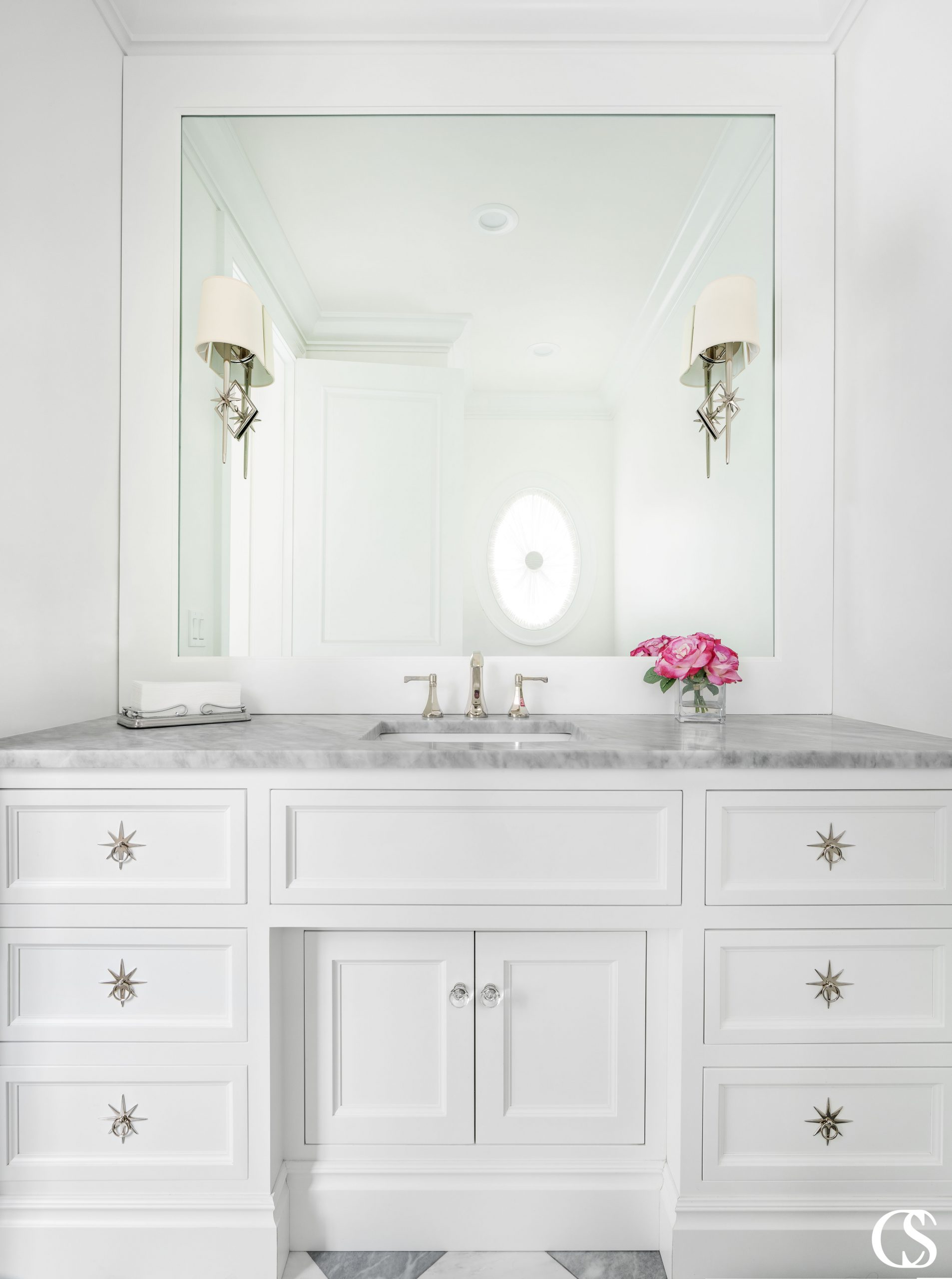 The unique starburst hardware adds such a unique flair to this white bathroom design. What kind of hardware would you pick?