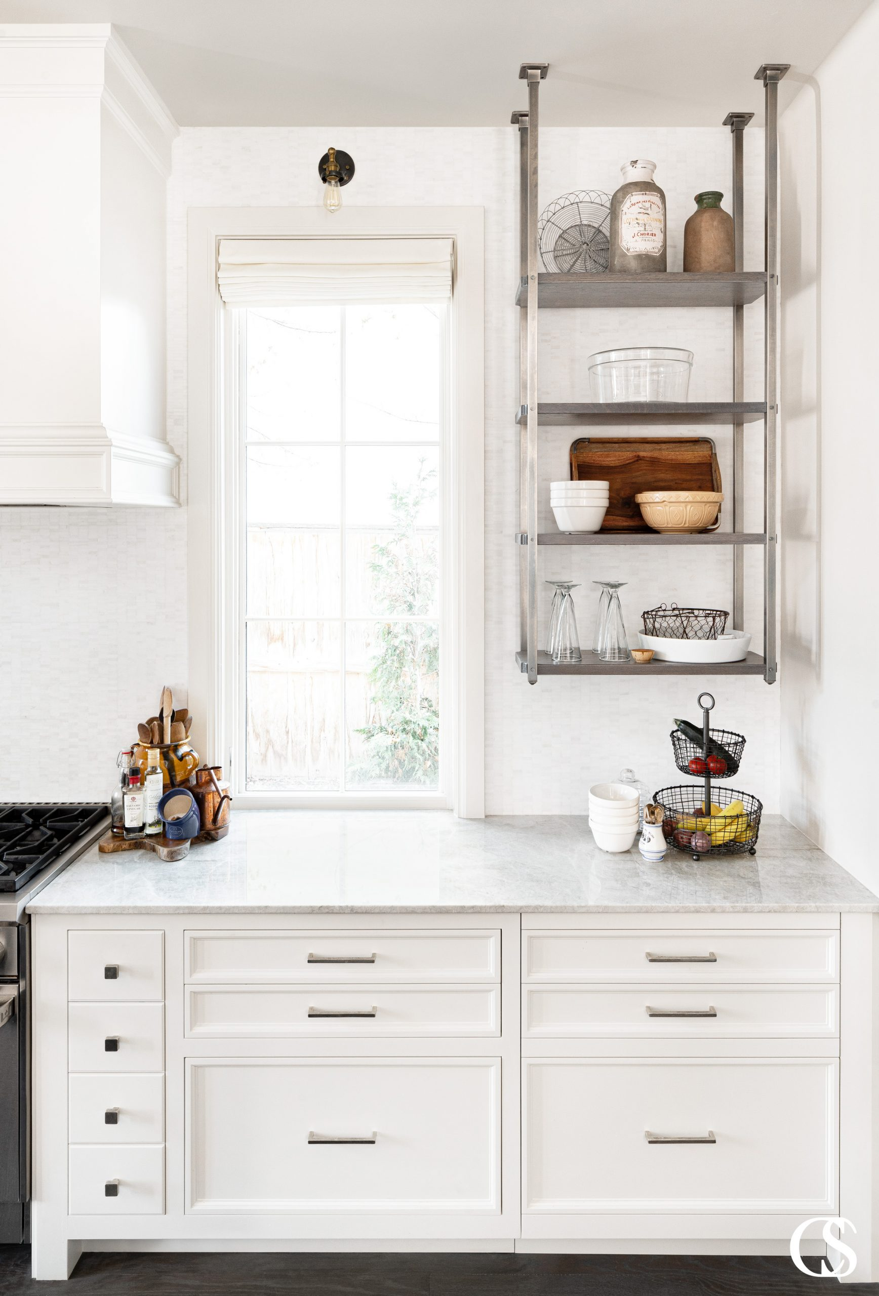 Custom kitchen cabinets design includes things like open industrial shelving and a range hood made to perfectly match the cabinets.