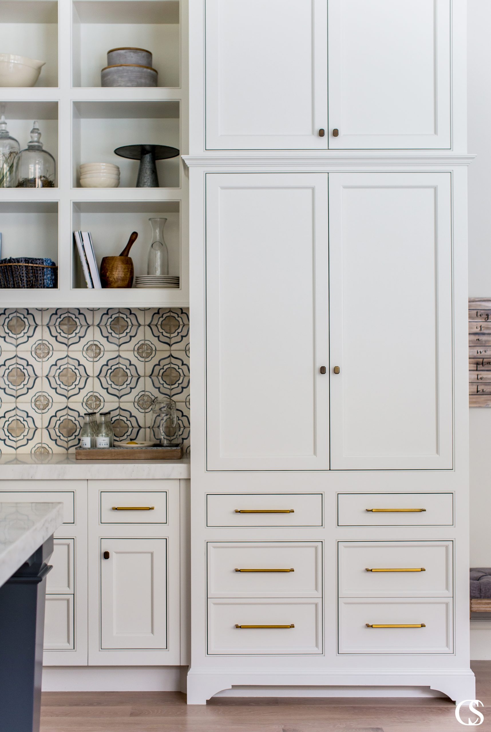 We love the combination of hardware styles mixed with a detailed tile backsplash in this set of custom white kitchen cabinets.